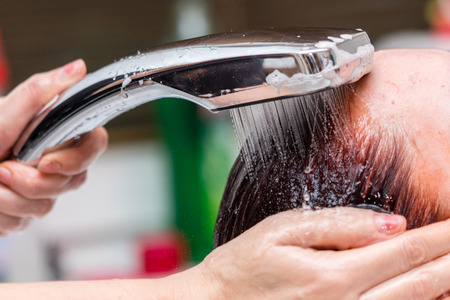 Hairdresser washing client hair. Closeup view.