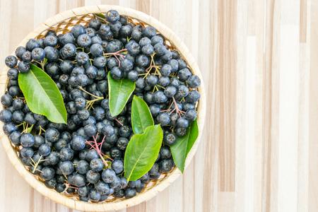 Fresh chokeberry (Aronia melanocarpa) in pot on wooden background 版權商用圖片