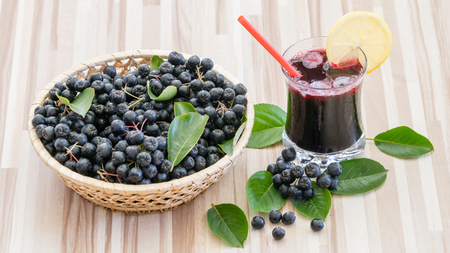 Fresh juice of chokeberry (Aronia melanocarpa) in glass and berry in pot on wooden background