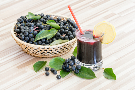 Fresh juice of chokeberry or Aronia melanocarpa in glass and berry in pot on wooden background Stock Photo
