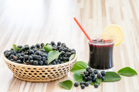 Fresh juice of chokeberry or Aronia melanocarpa in glass and berry in pot on wooden background Standard-Bild