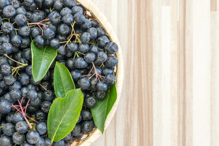 Fresh chokeberry or Aronia melanocarpa in basket on wooden background 版權商用圖片