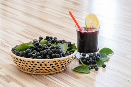 Fresh juice of chokeberry or Aronia melanocarpa with ice and lemon in glass and berry in basket near on wooden background