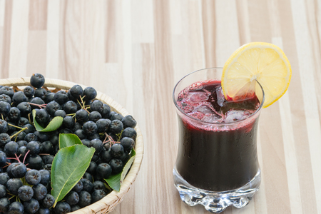 Fresh juice of chokeberry or Aronia melanocarpa in glass with ice and lemone slice, berry in basket on wooden background Standard-Bild