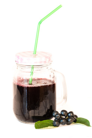 Fresh juice of chokeberry or Aronia melanocarpa in glass with straw and berry and leaves near, isolated on white background. Design element. Standard-Bild