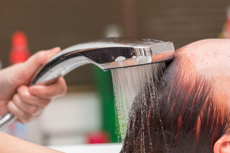 Hairdresser washing client hair after dyeing hair. Closeup view.