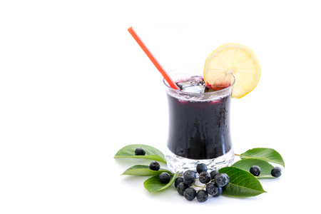 Fresh juice of chokeberry (Aronia melanocarpa) in glass and berry and leaves near, isolated on white background