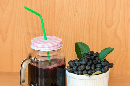 Chokeberry or Aronia melanocarpa juice with ice in glass with straw and berry in basket near on wooden background