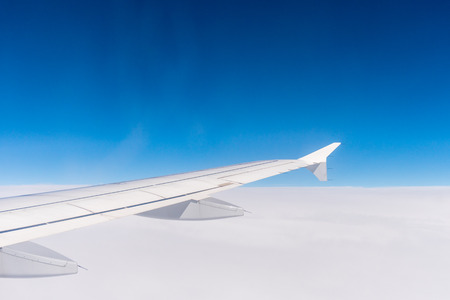 Wing of an airplane flying above the clouds. Window view of the blue sky. Aircraft wings. Standard-Bild