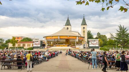 Medjugorje, Bosnia and Herzegovina- September 7.,2016., Pilgrims praying in pews before the holy mass in the outdoor shrine behind Saint James church.