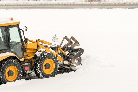 Snow removal. Wheel loader machine or vehicle removing snow from the roads in winter.