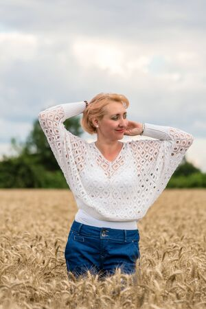 Beautiful romantic woman in white shirt and jeans stand in the golden wheat field. Happy summer or agriculture concept.