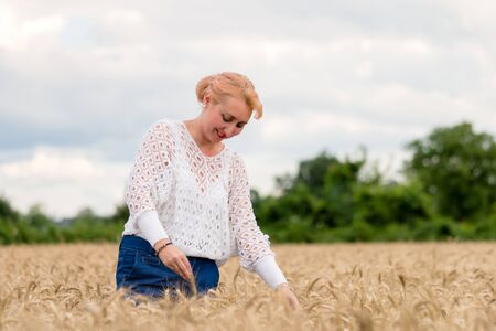 Beautiful woman stand in golden wheat field and hold ear of wheat, with cloudy blue sky background, free space. Liberty, peace of mind, happy summer or agriculture concept. 版權商用圖片