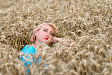 Portrait of beautiful woman with green eyes sitting in golden wheat field and look in the sky. Liberty, love, happy summer, peace of mind or relaxation concept.