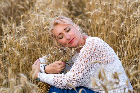 Beautiful woman with closed eyes sitting in golden wheat field and hug bunch of wheat ears. Liberty, love, happy summer, peace of mind or agriculture concept. Standard-Bild - 131434677