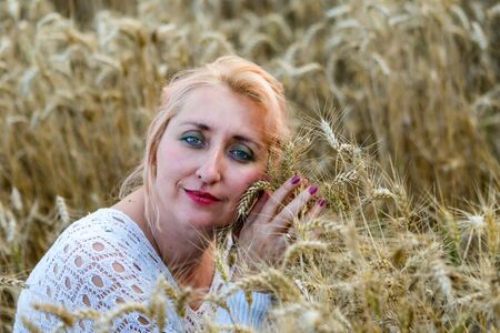 Portrait of beautiful woman with green eyes sitting in golden wheat field and hold bunch of wheat ears. Liberty, love, happy summer, peace of mind or agriculture concept.