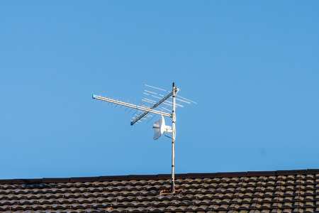 TV antenna on the house roof. Blue sky background. Фото со стока