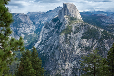 A view of the majestic Half Dome and the valley below from a viewpoint on the Glacier Point Hike trial, framed by the green of a tree.