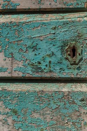 Un gros plan d'un trou de serrure rouillé sur une porte en bois ardoise peinte, la peinture bleu aqua est fanée et s'écaille