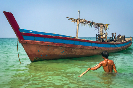 A fisherman wades out in waist deep water to his colourful wooden boat off the beach at Ngapali, Myanmar, against a clear blue sky
