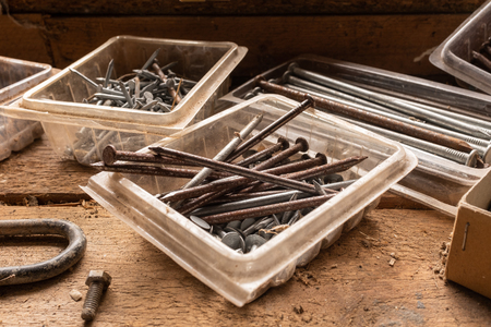 A close up of an assortment of nails and screws, some rusting on a wooden work bench, natural light