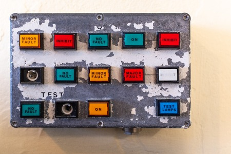 A small old control panel showing buttons of various colours on old paint peeling panel, nobody in the image