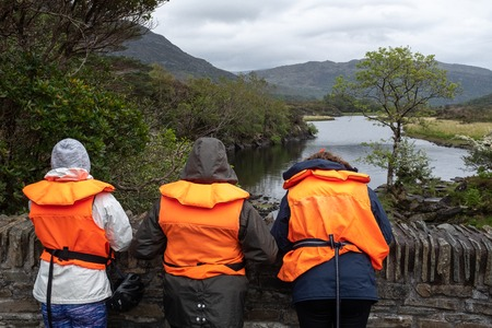 Three people waiting on a bridge wearing life jackets while they wait for a boat at the Meeting of the Waters, Ring of Kerry, Ireland, on an overcast day