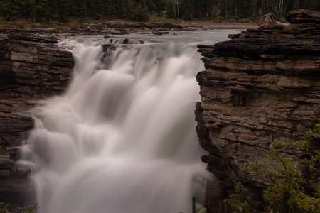 A close up of the mighty Athabasca Waterfall in Banff National Park, Canada, the torrent of water squeezes through a gap in rocks, long exposure to create blurred motion to the waterfall, nobody Standard-Bild