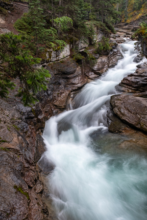 a beautiful waterfall cuts through the rocks at Maligne Canyon, Jasper National Park, Canada, long exposure to create blurred motion to the water, nobody in the image