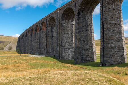 The sweeping majestic Ribblehead Viaduct stands tall above the Ribble Valley, Yorkshire, England carrying the Settle to Carlise railway against a bright blue sky