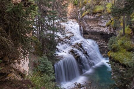 A waterfall shot from above and through some foliage, landscape aspect with a slow shutter speed.
