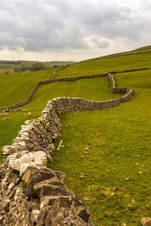 Dry stone walls snake their way into the distant green fields on the Yorkshire Moors near Malham, North Yorkshire, England