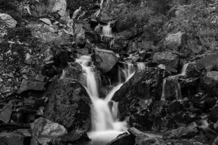A black and white image of a  small multii tiered waterfall just off the side of the road, long exposure shot to smooth out the cascading water