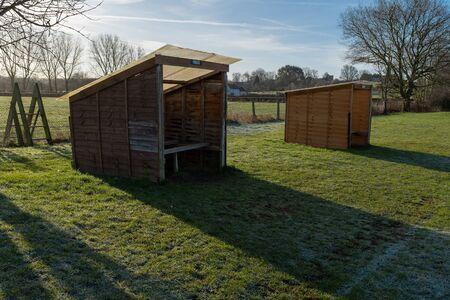 Two small rustic football dugouts in a field, with a clear blue sky in the background, the home dugout in the foreground Stockfoto - 126128975