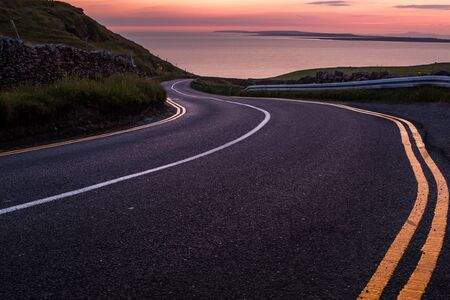 Looking down a sweeping road near the Cliffs of Moher to beautiful pink sky sunset over the island of Inisheer, nobody in the image