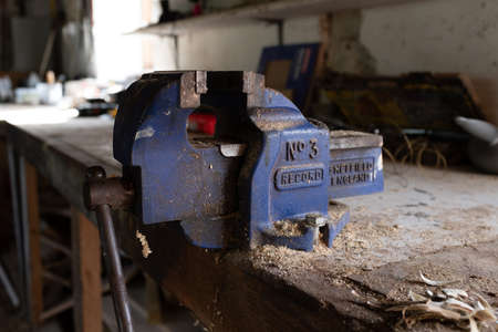 Ottery St Mary, Devon, Engalnd, March, 2, 2019: A close up of a used working bright blue vice on a wooden worktop in a workshop covered in wood cutting dust 報道画像