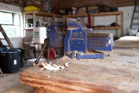 A close up of a blue vice on a wooden worktop in a workshop covered in wood cutting dust