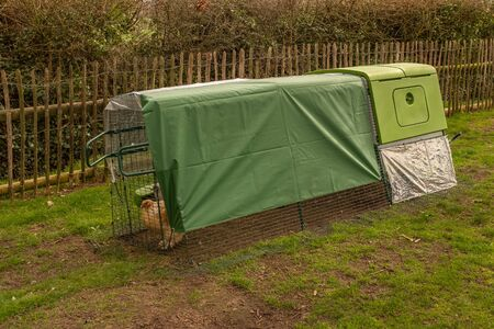 A full length shot of a green modern bright looking chicken coup or hen house with covered top