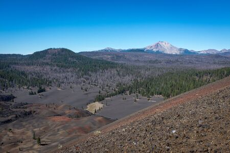 At the top of Cinder Cone, Lassen National Park looking out across the landscape to a mountain in the distance, bright blue sky