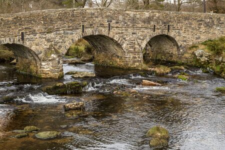 A side view of the stone Pack Horse bridge over the East Dart River in Dartmoor National Park, England with nobody crossing the bridge