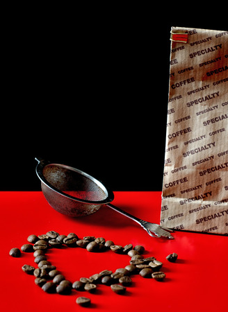 bolter: coffee beans and sieve on the Red surface Stock Photo
