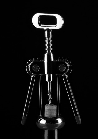 Corkscrew for wine and cork on black background. Stock Photo