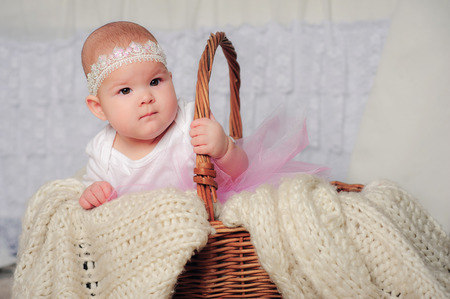 babycare: cute little girl in basket with lace headband