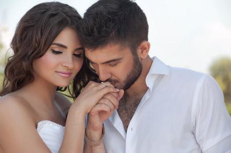 groom and bride: groom in white shirt kiss bride hand. Very gentle photo