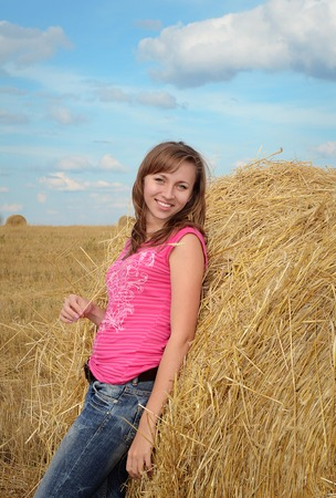 casual wear: Attractive smiling young woman in casual wear near the haystack