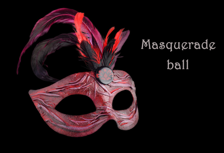 masquerade ball: Venetian red Carnival half mask with feathers  on black background.  Text Masquerade ball Stock Photo
