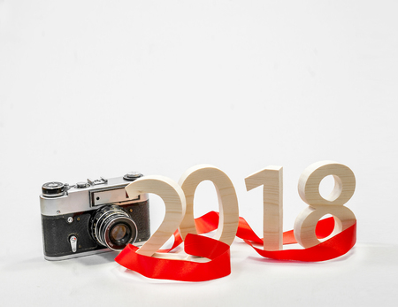 Figures 2018 carved from wood with a vintage camera. Concept of a New Years postcard, poster. Photo Trends Stock Photo