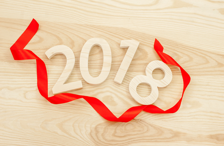 New Years concept. Figures 2018 carved from wood on the background of a polished board framing a red ribbon Stock Photo