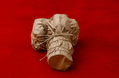 Digital camera wrapped in craft paper rewound with cord on red background. Gift, surprise, packaging. Copyspace.