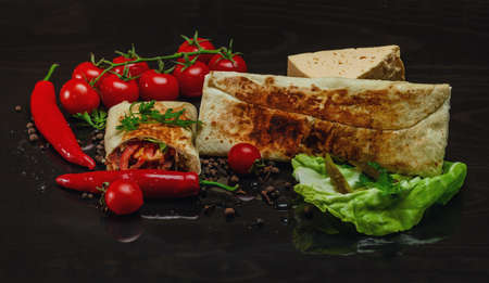 Composition of shawarma, red pepper, cherry tomatoes, cabbage, cheese on a black wood background.